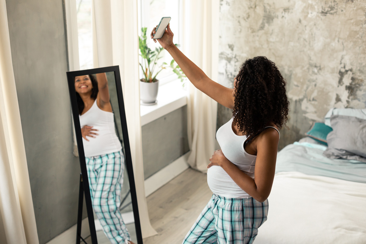 Pregnant woman takings selfie - 10 Reasons to Document Your Pregnancy After Loss With Shameless Selfies