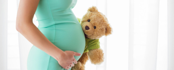 Pregnant woman holding teddy bear - Pregnancy After Loss Bill of Rights