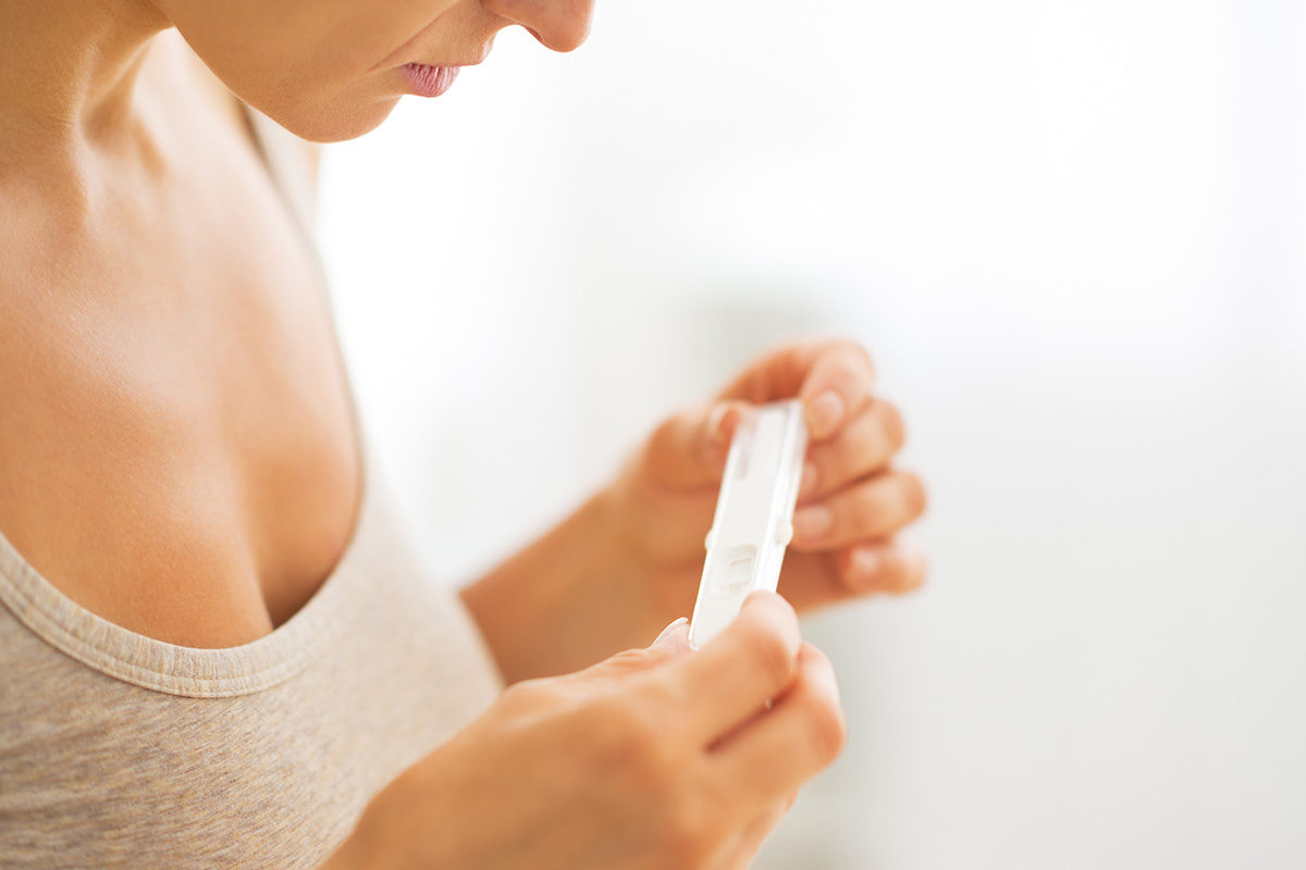 woman looking at pregnancy test - 10 Things I Want You to Know about Trying to Conceive after a Loss