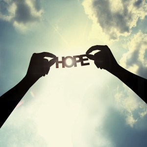 Holding the word hope silhouette blue sky