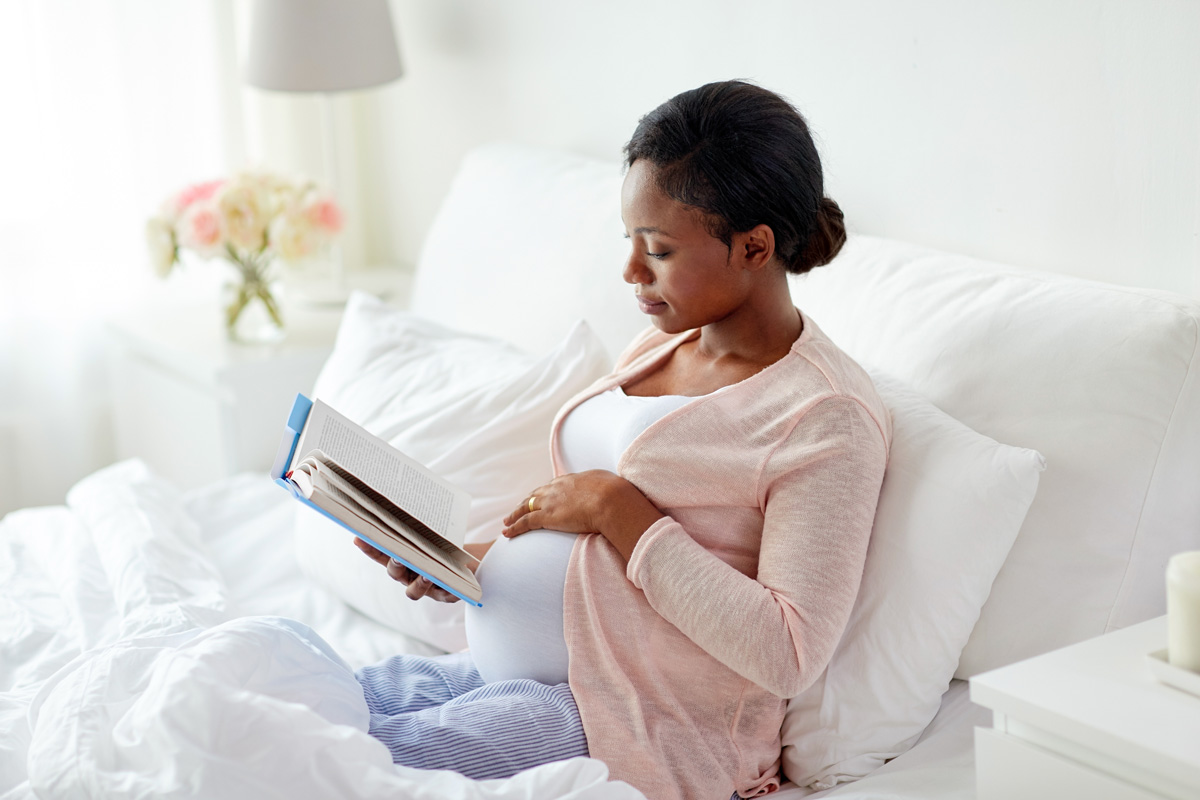 pregnant woman reading in bed - Tips from PAL Moms: Childbirth & Parenting Classes during Pregnancy After Loss