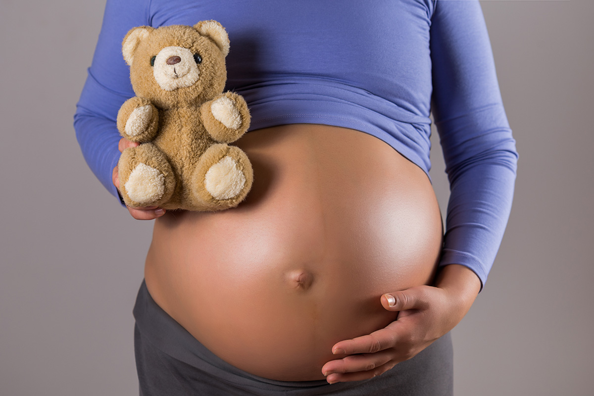 pregnant woman holding teddy bear - How remembering your baby helps you bond with the next one