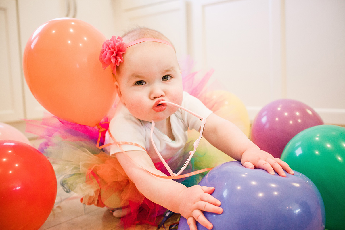 first birthday girl playing with balloons - Why I Throw Shameless Over-the-Top Birthday Parties for my Kids