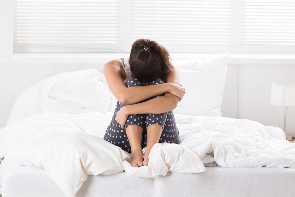woman crying on bed - the morning after the miscarriage