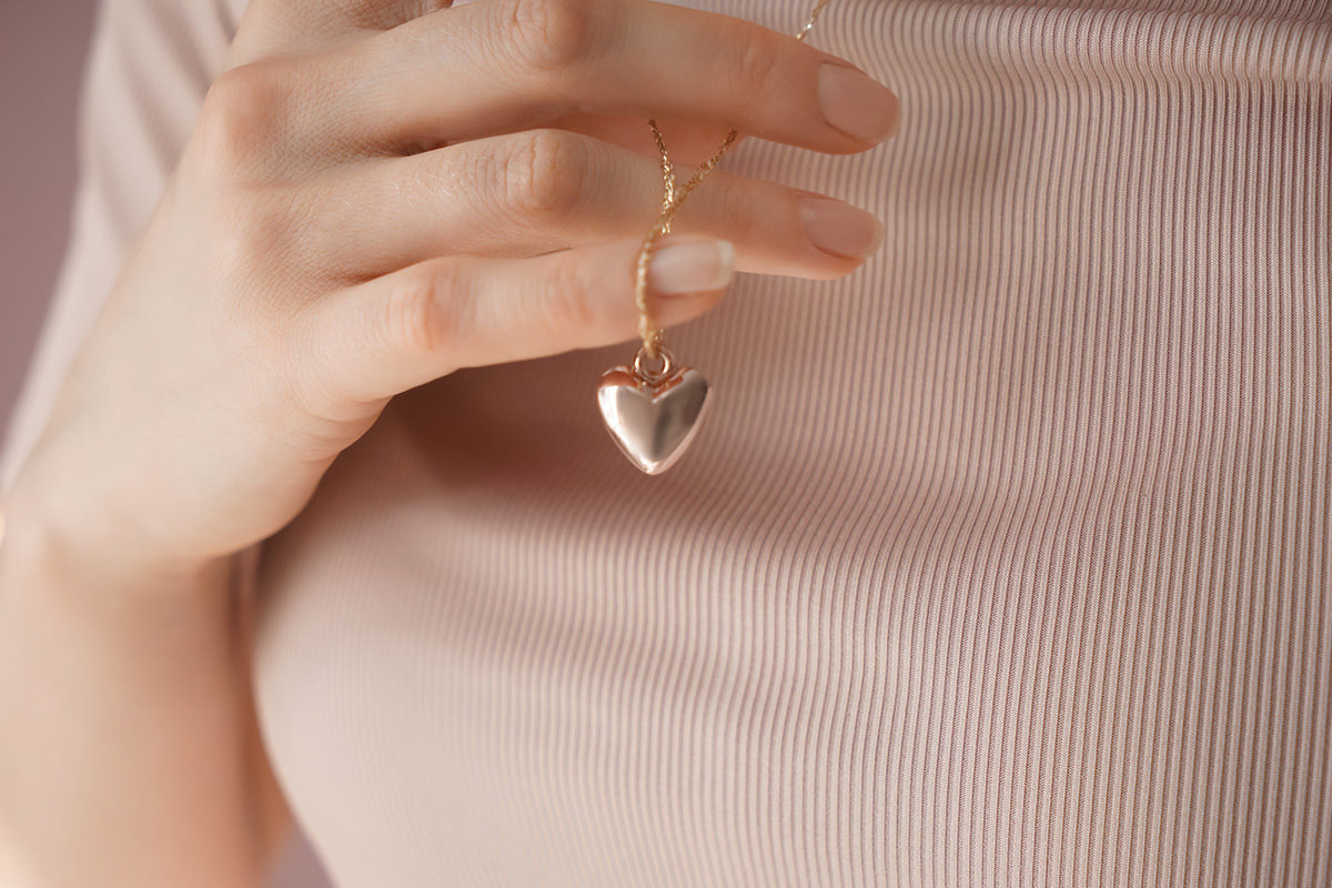 Woman holding necklace - Invisible Motherhood