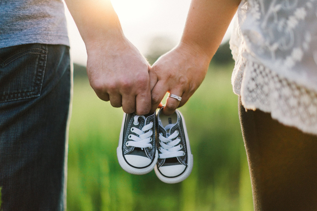couple holding baby shoes - my husband carried the weight of my pregnancy after loss
