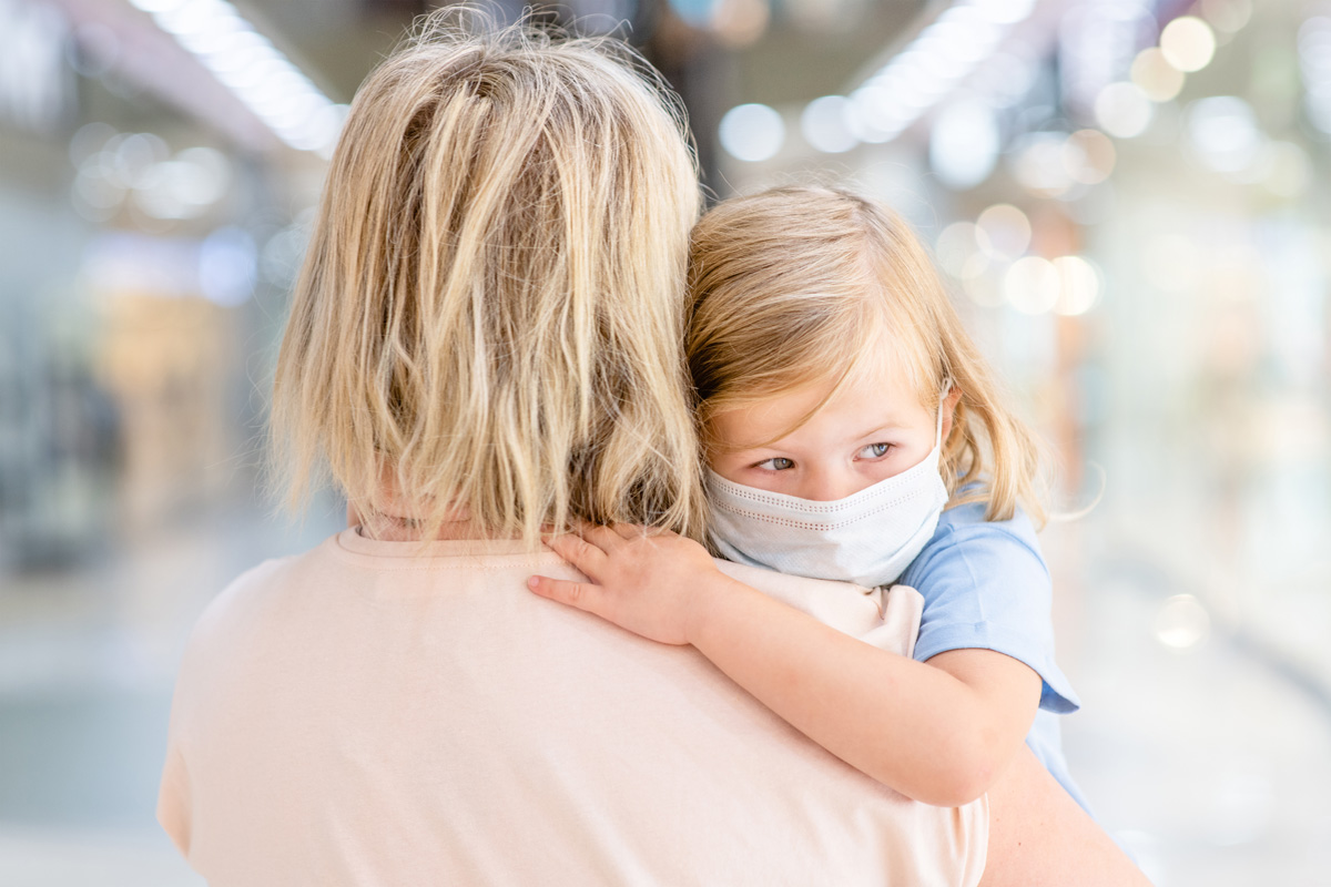 child in mask being held by mom - Why Evaluating Risk is Different for Loss Parents