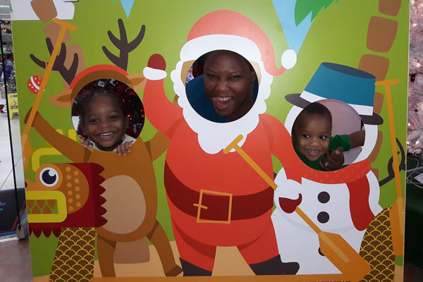 mom with kids with Christmas cut-out - Christmas lives on through our rainbow babies