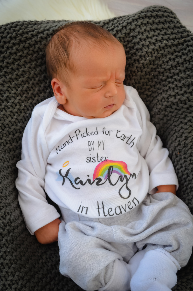 """Kaizden Otto Wayne wearing a onesie that says, """"Hand-Picked for earth by my sister in Kaizlyn in Heaven"""
