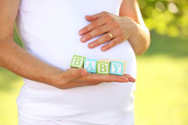Pregnant woman holding baby blocks - Creating the Perfect Baby Name After Loss