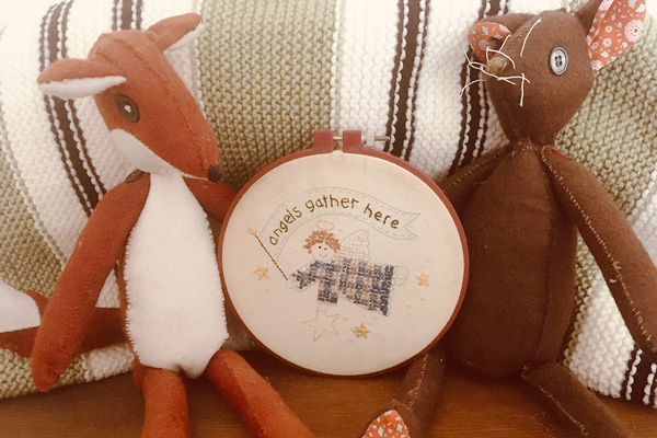"stuffed animals with ""angels gather here"" embroidery - Libby's Bump Day Blog, Week 30: Dusting off the Baby Gear"