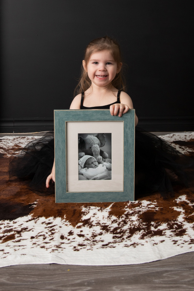toddler holding photo of brother - Mary's 37-week bump day blog: Delivery Day and Reflection