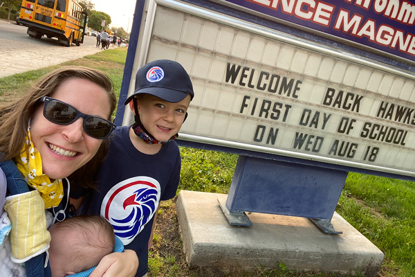 Family at first day of school sign